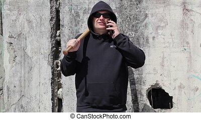 Man with a baseball bat talking on smart phone