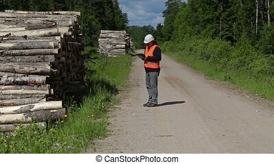 Lumberjack writing and walking near log of pile