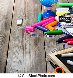 Assortment of office and school supplies on wooden table -...