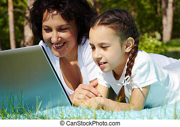Wireless Internet - Portrait of mother and daughter looking...