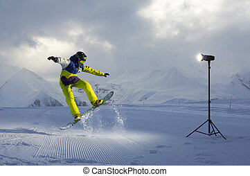 photoshoot snowboarder who jumps. artificial light from...