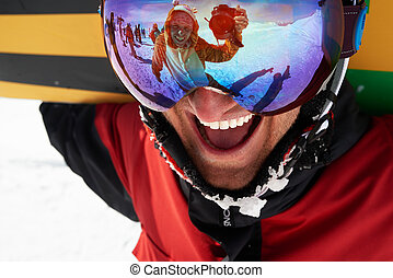 Happy snowboarder in mask with friend taking shot in...