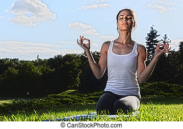 Young woman during yoga meditation in the park.