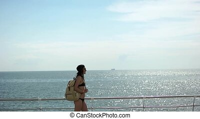 Girl with backpack at the sea