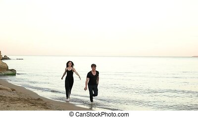Couple running barefoot on the beach