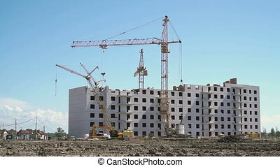 Construction cranes works on the construction site -...
