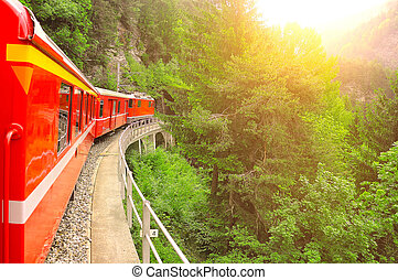 Passenger train at sunset. - Passenger train moves from Chur...