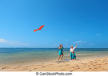Grandmother, mother, and child launching kite on sea beach