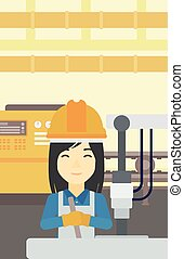 Woman working on industrial drilling machine - An asian...