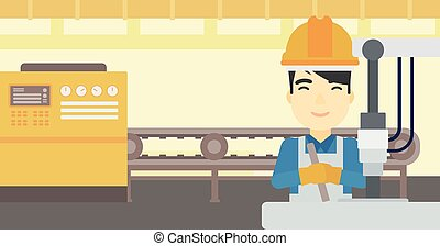 Man working on industrial drilling machine - An asian man...