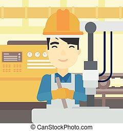 Man working on industrial drilling machine. - An asian man...
