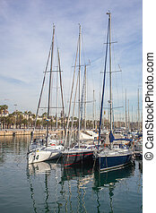 Row of luxury yachts mooring in a harbour in Barcelona,...