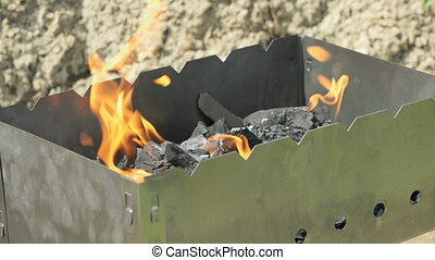 Flames with sparks on the coals in the grill outdoors