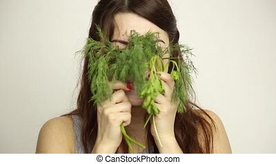 beautiful young woman eating an vegetables. holding dill and parsley. healthy food - healthy body concept