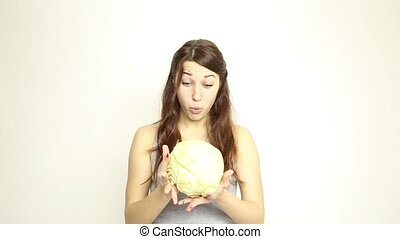 beautiful young woman eating an vegetables. holding cabbage, she stares at the head of cabbage. healthy food - healthy body concept