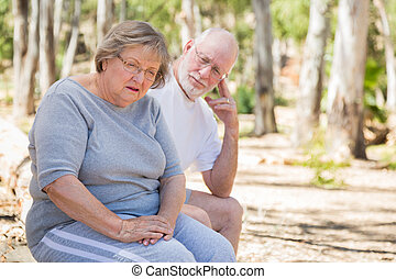 Upset Senior Woman Sits With Concerned Husband Outdoors -...