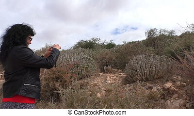 Woman taking picture of cactus - Woman with black curly hair...