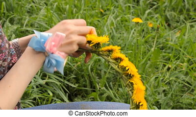 Woman weaves a wreath of dandelions in the summer park