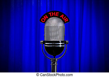 Microphone on stage with spotlight on blue curtain - Retro...