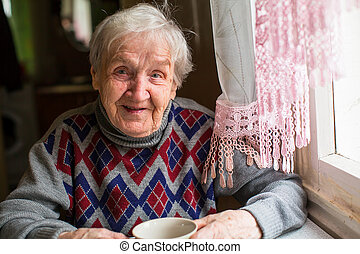 Happy elderly woman portrait sitting at the table in the...