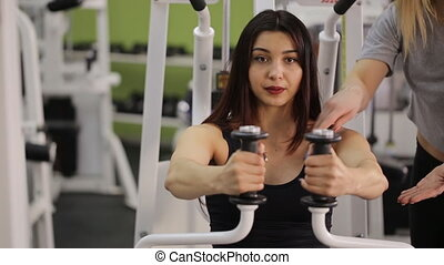 Sportive woman does exercises under guidance of coach in gym.