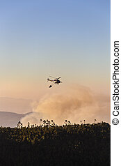 fire-fighting helicopter with a water bucket fighting a fire...