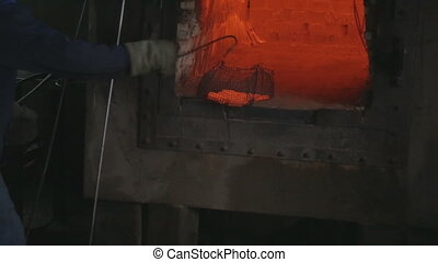 Factory worker puts hot pieces of metal in a container of...