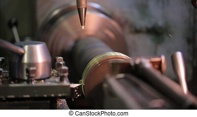 Coolant drips on a rotating metal workpiece clamped in machine for processing.