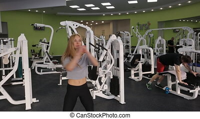 Beautiful blonde woman does exercises in gym in day time.