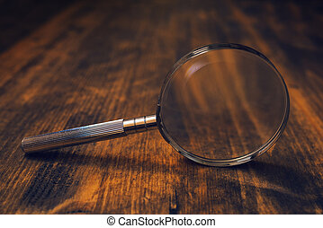 Loupe magnifying glass on wooden desk, concept of searching...