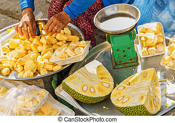 Asian woman selling flesh of cleaned durian in Hoi An -...