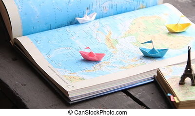 Travel and tourism idea. Paper boats on the map and the...