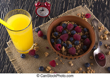 Muesli with fresh berries, orange juice and alarm clock.