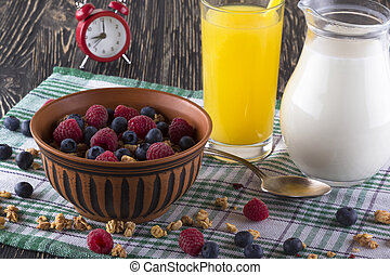 Muesli with fresh berries, orange juice, milk and alarm clock.
