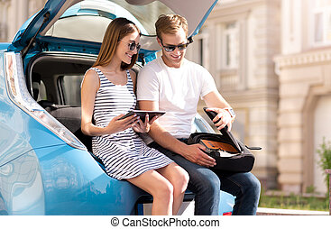 Couple sitting on trunk of car