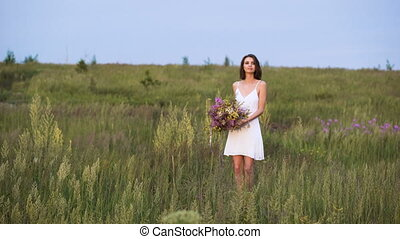 Young girl walks on a sunset on summer field with a bouquet of flowers.
