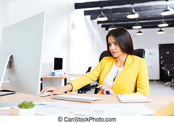 Portrait of a serious businesswoman using laptop in office -...
