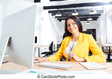 Portrait of a smiling businesswoman using laptop in office -...