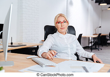 Portrait of a smiling mature businesswoman using laptop in...
