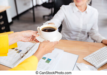 Cropped image of secretary with coffee cup - Cropped image...