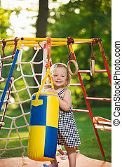 The little baby girl playing at outdoor playground against...