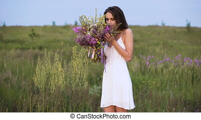 Young girl walks on a sunset on summer field with a bouquet...