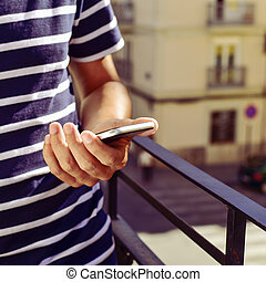 young man using his smartphone in the balcony - closeup of a...