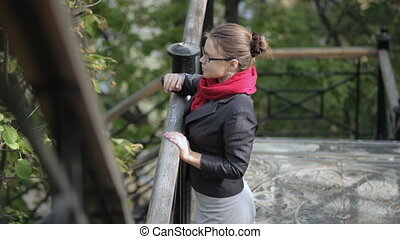 Woman in glasses standing near railing and looks into distance