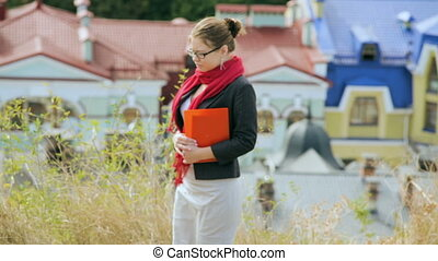 Young blonde woman with folders in the hand, outdoors in...