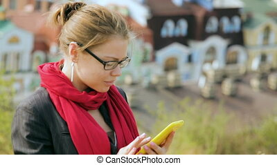 beautiful woman in glasses is typing on smartphone