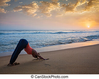 Woman doing yoga Surya Namaskar oudoors at tropical beach -...