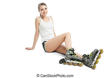 Pretty happy girl with rollerskates sitting on floor against...