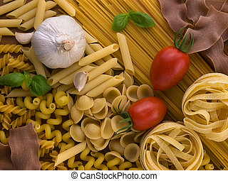 different kind of raw pasta with tomatoes garlic and basil