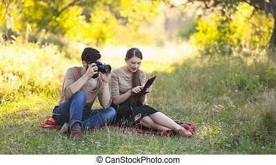 young couple with a tablet and camera